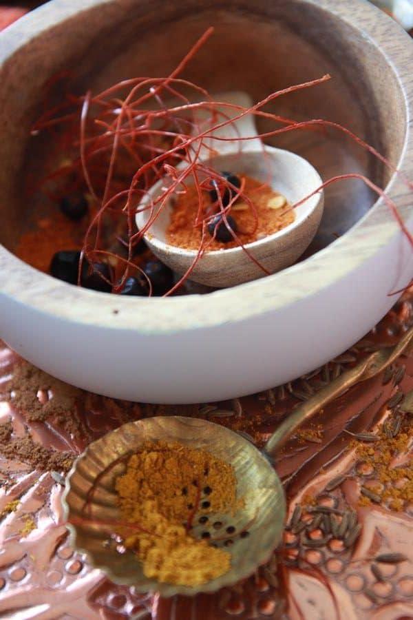 Chilifäden und Curry, Wacholderbeeren, hellgraue Servierschale, Messinglöffel, Kupferteller, orientalische Gewürze. © Copyright Bettina Katscher 2020