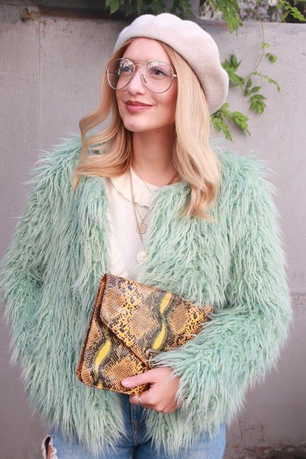 Frau mit mintfarbener Fake Fur-Jacke, Pythonprinttasche, beiger Baskenmütze, goldfarbene Ketten mit Emblem und cremefarbenem Volantspullover. © Copyright Bettina Katscher 2020