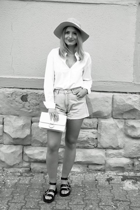 Sommerlook, Strohhut, schwarze Sandalen mit runden Schnallen, weiße Bluse, cremefarbene Handtasche, goldfarbener Schmuck. © Copyright Bettina Katscher 2020