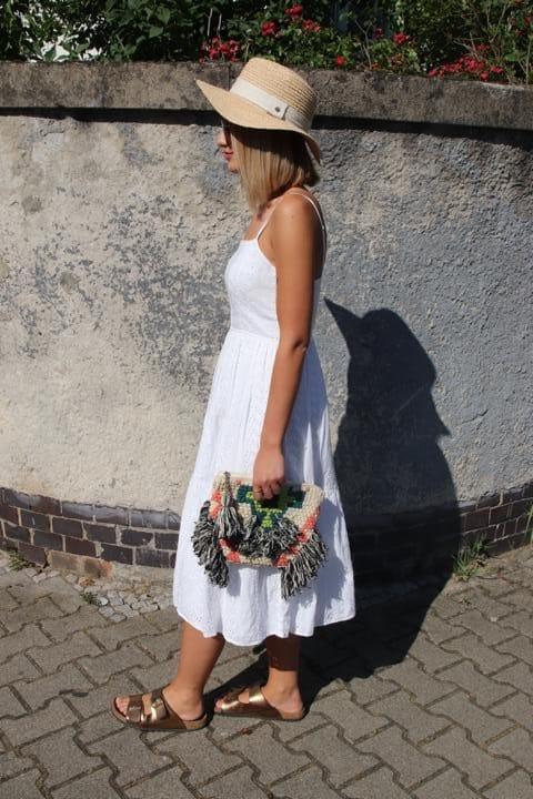 Strandlook mit Strohhut, Boho-Tasche mit Fransen und Ethnomuster, weißem Sommerkleid mit Spaghettiträgern und goldenen Birkenstocks. © Copyright Bettina Katscher 2020
