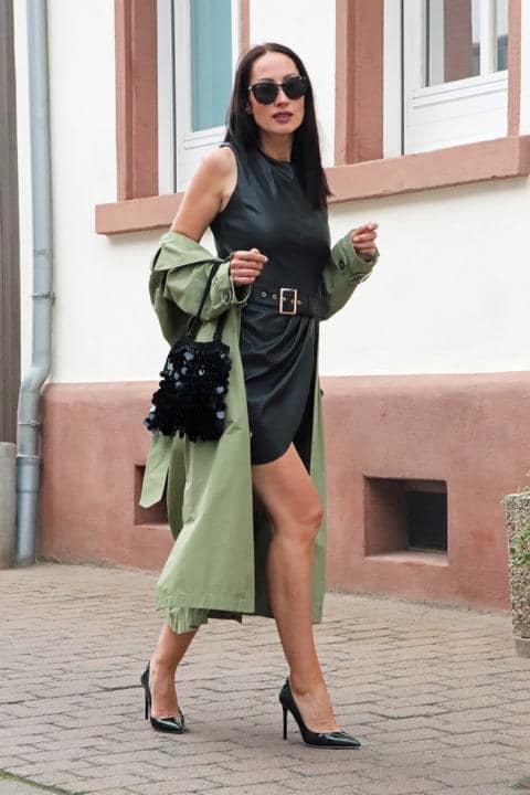 Sexy Sommerlook, der aus einem grünen Trenchcoat, einem schwarzen Lederkleid und Lack-Highheels sowie einer Paillettentasche besteht. Lack, Leder und Pailletten machen den Look aus. © Copyright Bettina Katscher 2019