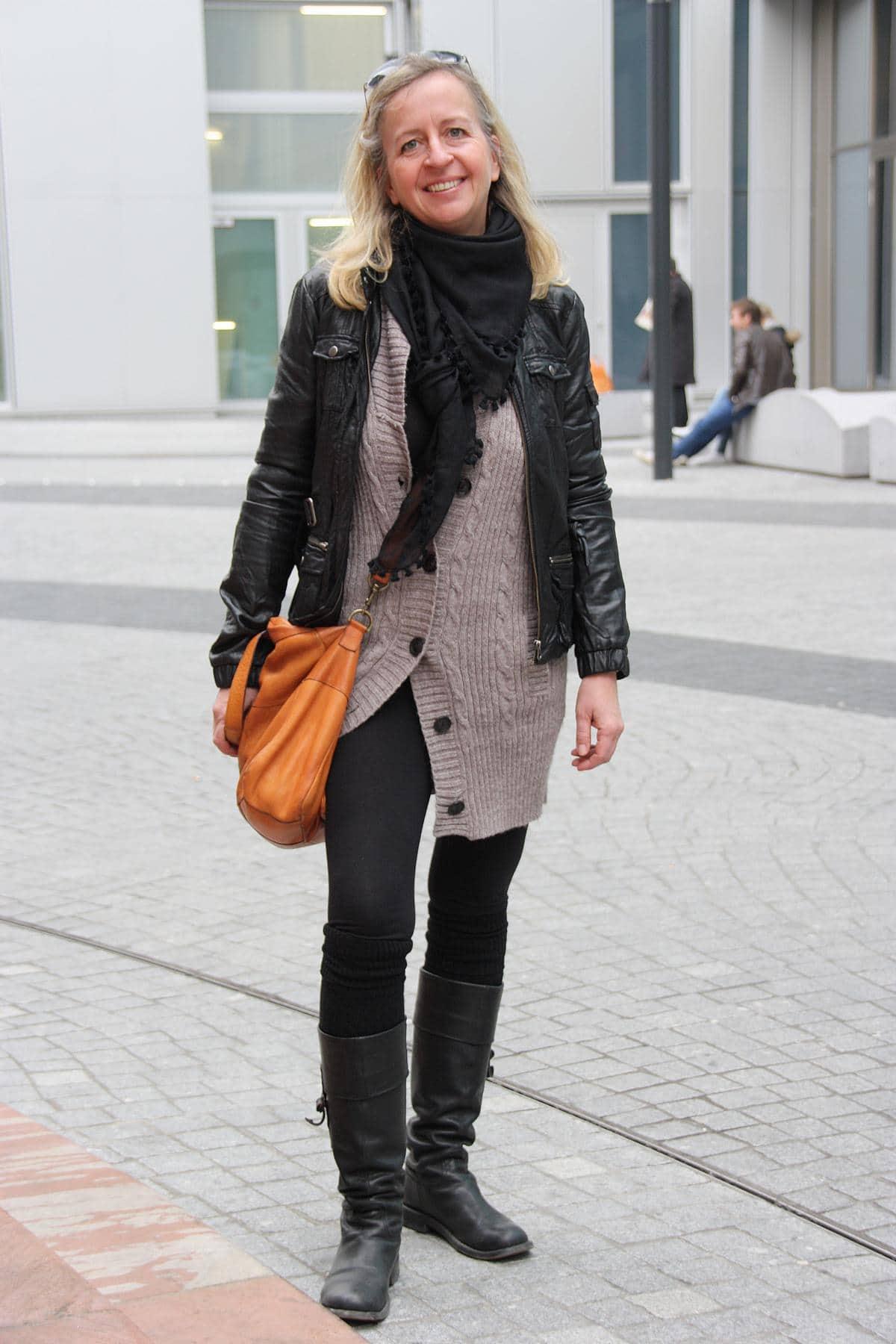 Legerer Streetstyle-Look mit schwarzen Stiefeln, Leggins, Strickcardigan und Lederjacke in Schwarz und Beige, dazu eine Crossbody-Bag in Cognac. © Copyright Bettina Katscher 2019