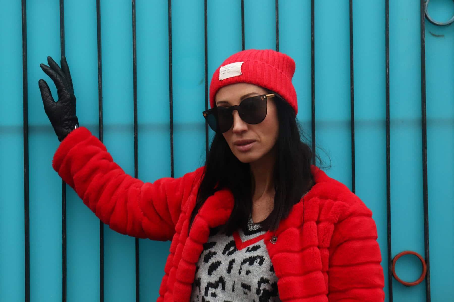Herbst-Winter-Style a la Apres-Ski mit roter Fake Fur-Jacke, Leo-Strickpullover mit Silber und Designerhandschuhen sowie Designersonnenbrille. © Copyright Bettina Katscher 2019