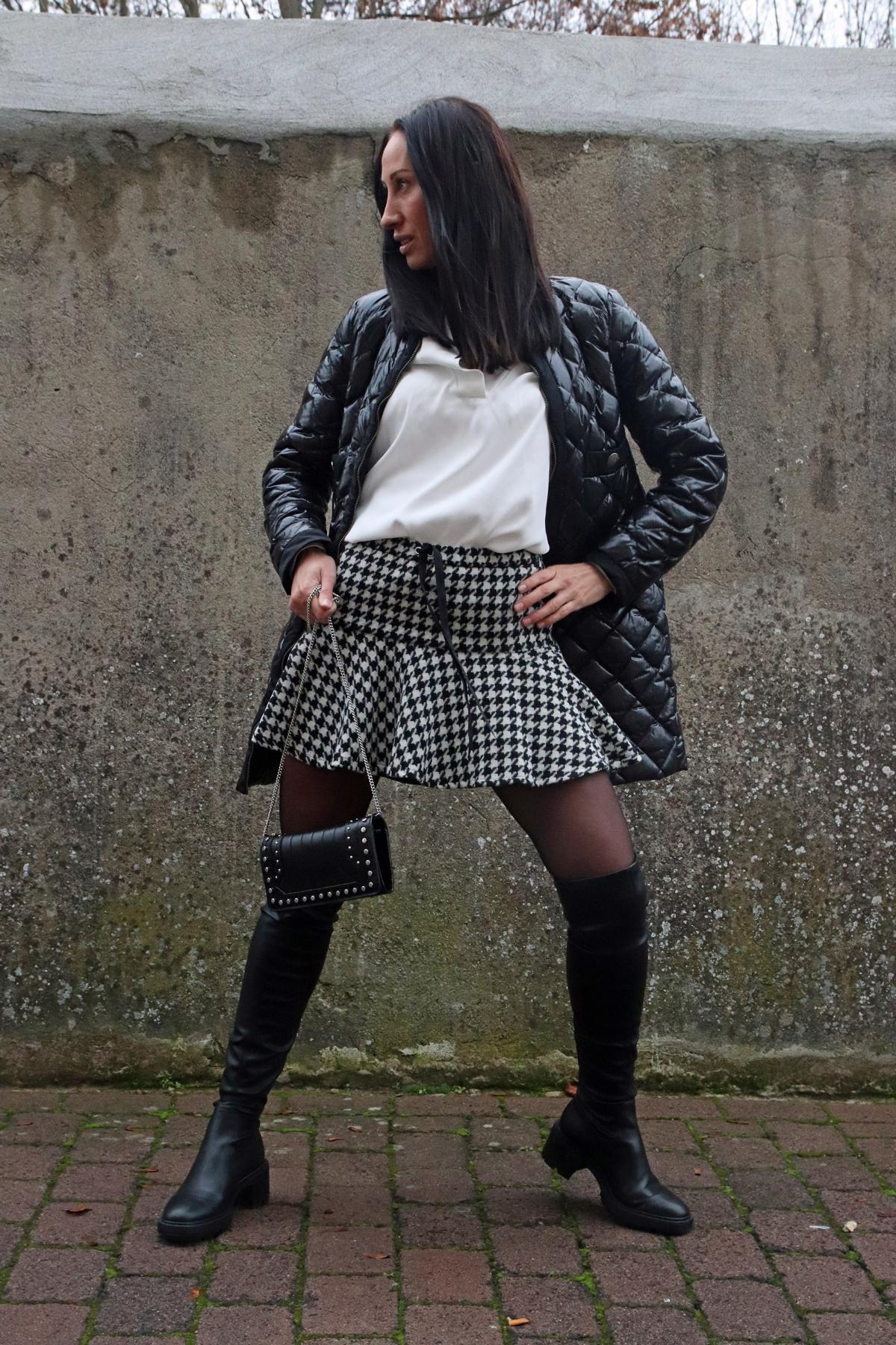 Streetstyle für Damen in Schwarz-Weiß, bestehend aus Hahnentritt-Minirock, falchen Overknees aus Leder, Mini-Nietenhandtasche und Luxus-Steppjacke. © Copyright Bettina Katscher 2019
