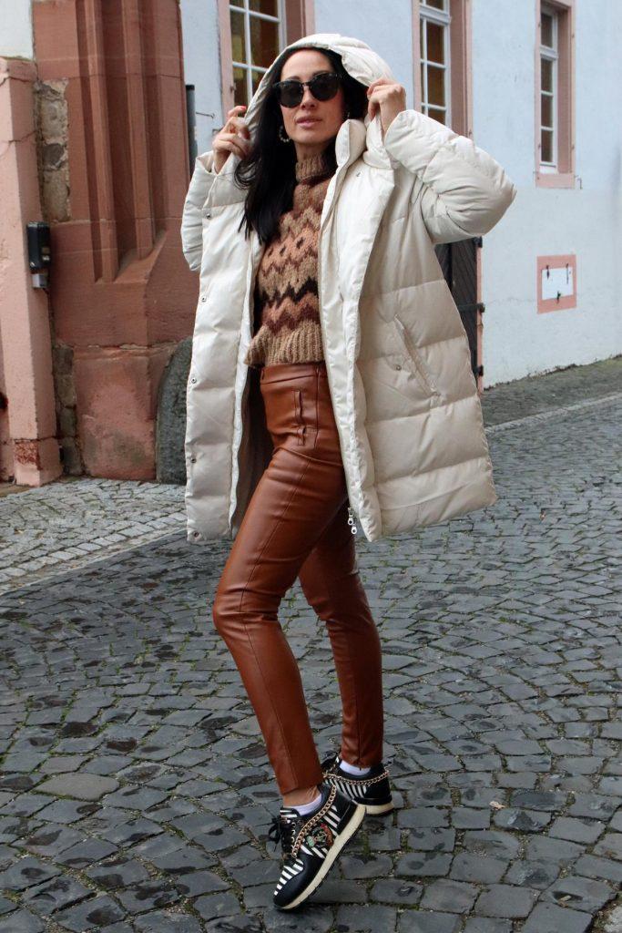 Winter-Bloggerstyle in Camel, Creme und Schwarz. Eine Kombination mit Lederleggins, auffälligen Sneakern mit Streifen und Gliederkette, Norwegerpullover sowie einer oversized Jacke. Diese Jacke ist eine Steppjacke in Creme, die perfekt zum Aufwärmen ist. Das Model trägt außerdem eine Designersonnenbrille. © Copyright Bettina Katscher 2019