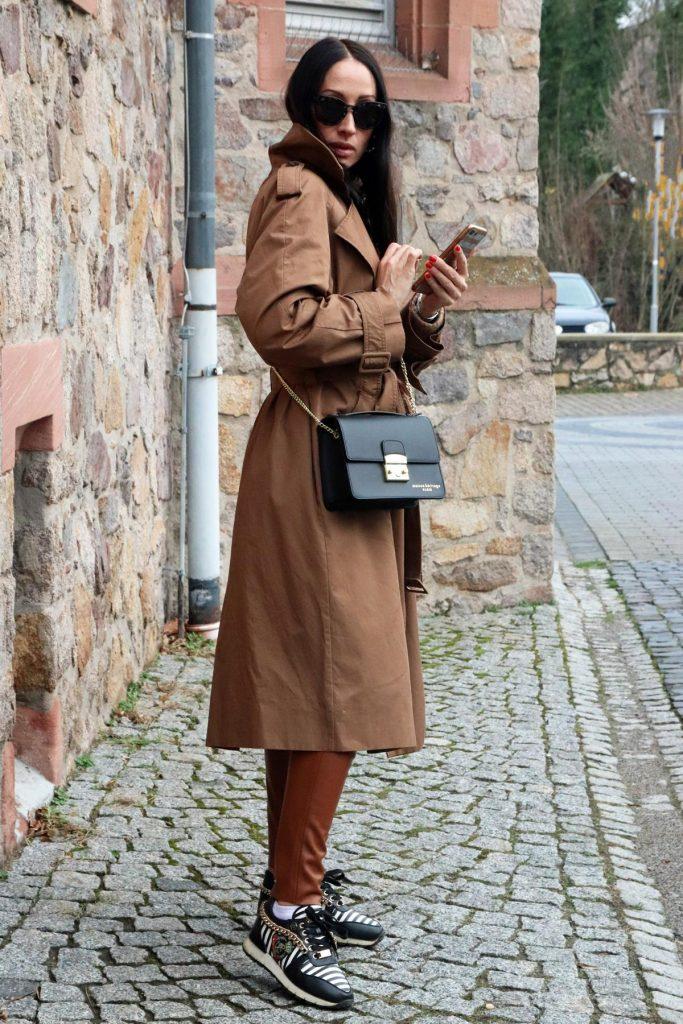 Blogger-Herbstlook in Camel, bestehend aus einer Lederoptik-Leggins, Designersneakern mit Streifen, Emblem und Goldkette sowie klassischem Trench und klassischer schwarzer Handtasche in Kastenform. © Copyright Bettina Katscher 2020