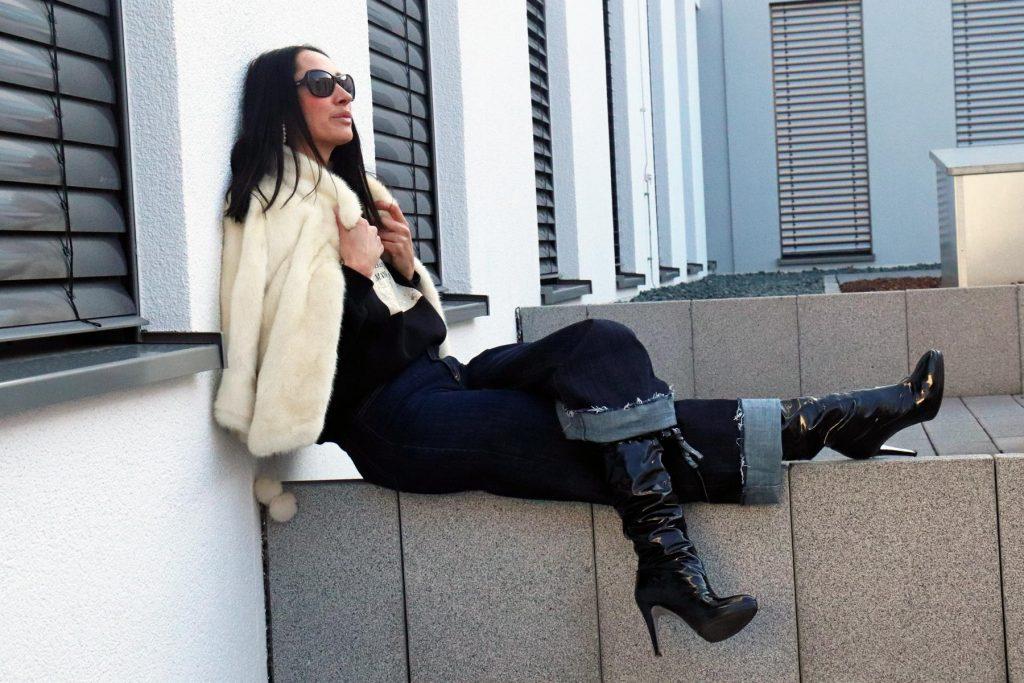 Blogger-Winterstyle bestehend aus einer Schlaghose aus dunklem Denim, dazu eine helle Pelzjacke, schwarzes Shirt und hohe Lack-Stiefel zum Binden. © Copyright Bettina Katscher 2020