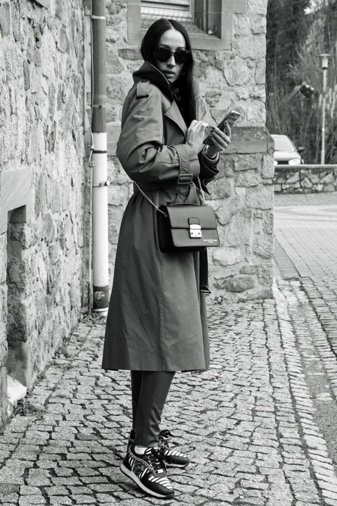 Repost in Schwarz-Weiß: Herbst-Bloggerstyle in Camel und Schwarz mit klassischen Trenchcoat, auffälligen Sneakern und klassischer Damentasche mit Gliedergurt. © Copyright Bettina Katscher 2020