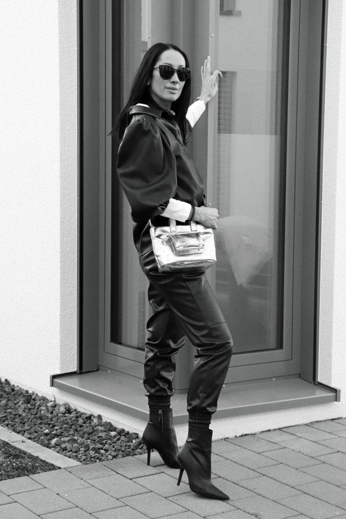 Blogger-Winterlook in Schwarz, Weiß und Silber, der sportlich und sexy ist, mit Leggins und Bluse in Lederimitat, spitzen hohen Stiefeletten und silberner Handtasche plus Designersonnenbrille. © Copyright Bettina Katscher 2020