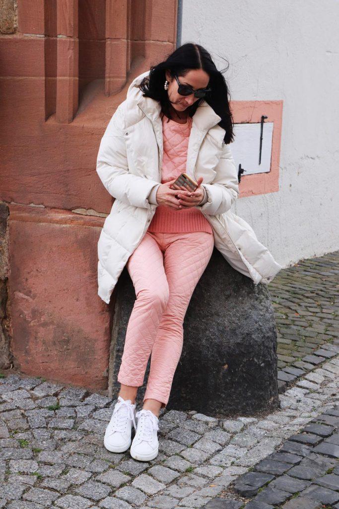 Blogger-Streetstyle-Look fürs Frühjahr in Rosa und Weiß, wobei die Hose und der Pullover mit Rauten-Steppnähten verziert sind. Dieser Look ist auch was für Sneaker-Fans. © Copyright Bettina Katscher 2020