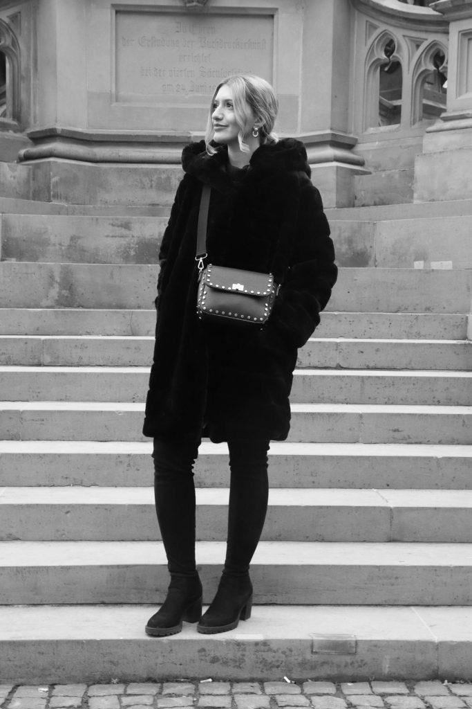 Repost in Schwarz-Weiß: Blogger-Streetstyle mit Overknees, Fake-Fur Mantel und schwarzer Kasten-Handtasche mit Nieten in Gold. © Copyright Bettina Katscher 2020