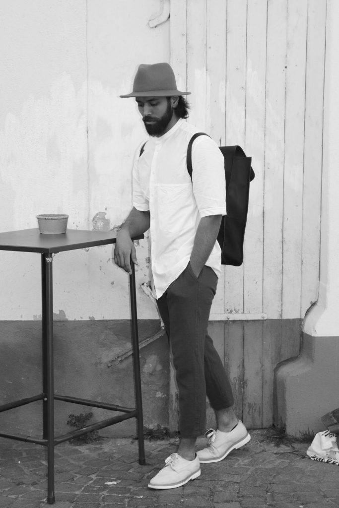 Man Fashion in Street Style Look aus Stoffhose, hellen Schnürschuhen mit Tasseln, weißem Hemd, Hut und Rucksack. © Copyright Bettina Katscher 2020