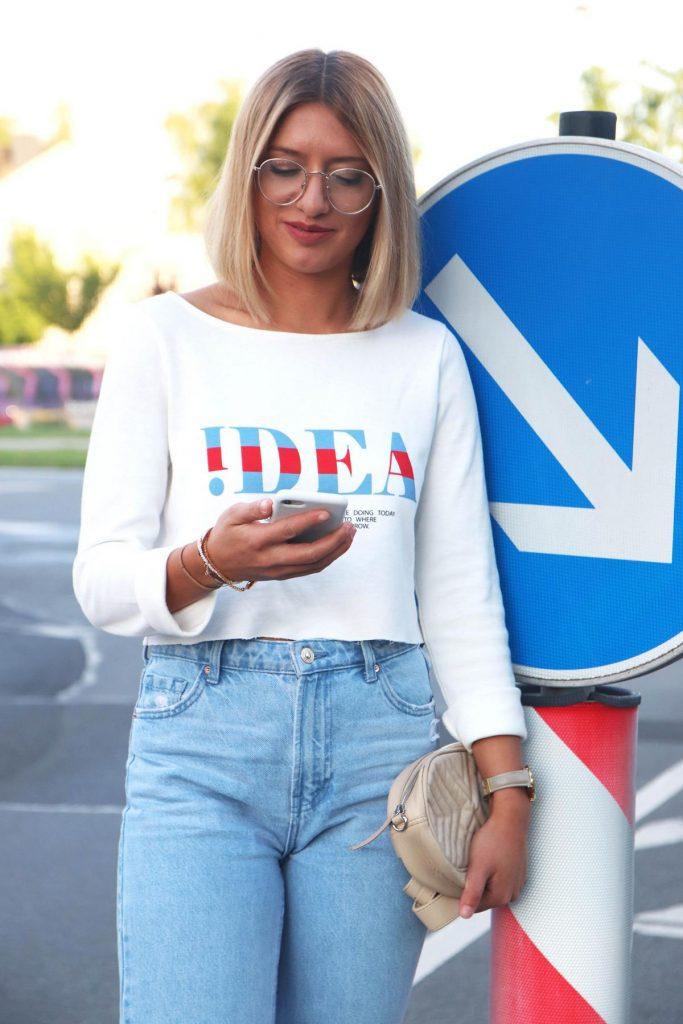 """Sportlicher Streetstyle Look in Blau Weiß Rot mit Jeans und Sweatshirt mit Schriftzug """"IDEA"""" und beiger Gürteltasche mit Steppnähten. © Copyright Bettina Katscher 2020"""