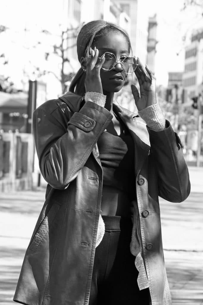 Graue Retro-Lederjacke für Damen mit sportlichem Look aus cropped Shirt und Jogginghose und sechseckiger pinker Sonnenbrille. © Copyright Bettina Katscher 2020