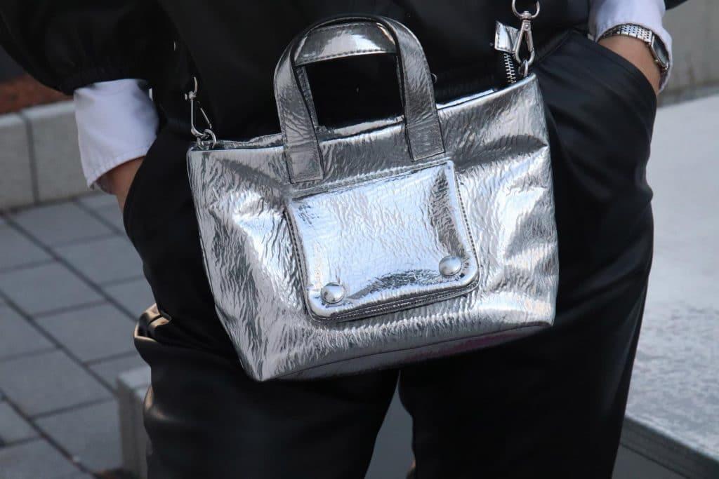 Metallic-Handtasche mit auffälligem Gurt und Aufsatztäschchen mit Druckknöpfen, dazu eine schwarze Hose in Lederimitat und eine klassische Damenuhr. © Copyright Bettina Katscher 2020