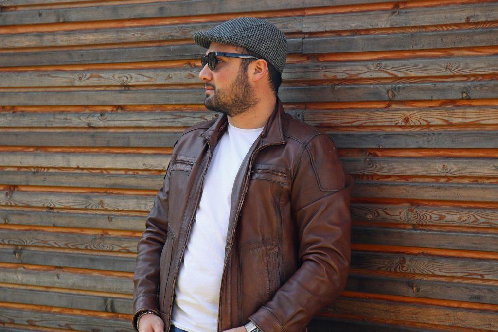 Man Fashion für Streetstyle Look mit brauner Lederjacke, karierter Kappe, weißem T-Shirt und Sonnenbrille. © Copyright Bettina Katscher 2020
