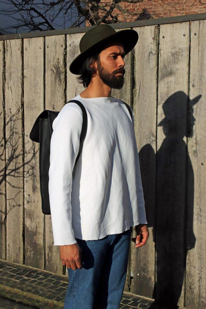 Minimalistische Man Fashion mit cleanem weißem Sweatshirt mit abgeschnittenen Bündchen, blauer Jeans, schwarzem Rucksack und grünem Hut. © Copyright Bettina Katscher 2020