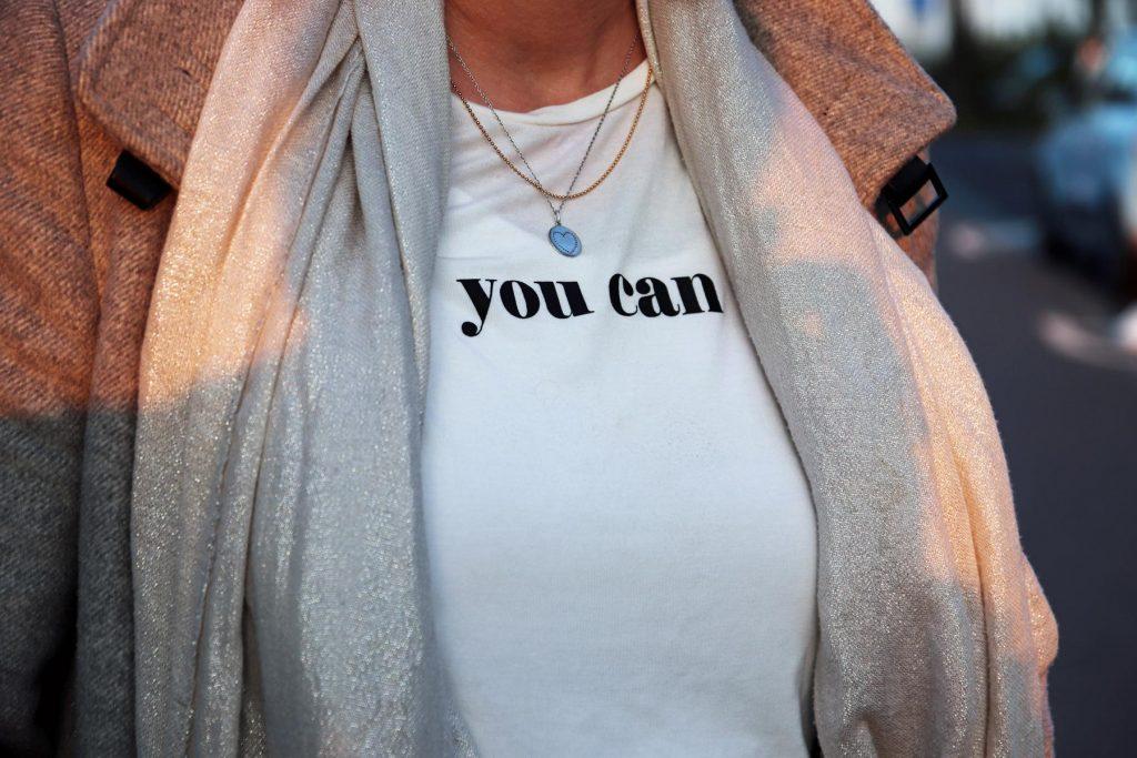 """Statement-T-Shirt in Creme mit dem schwarzen Schriftzug """"you can"""", silbernem Schal und grauem Mantel. © Copyright Bettina Katscher 2020"""