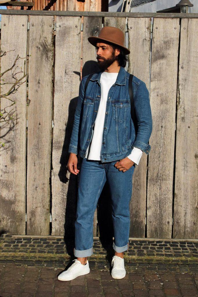 Reduziert auf Basics: Man Fashion mit cleanem weißem Sweatshirt mit abgeschnittenen Bündchen, blauer Jeans, blauer Jeansjacke, beigem Hut und schwarzem Rucksack. © Copyright Bettina Katscher 2020