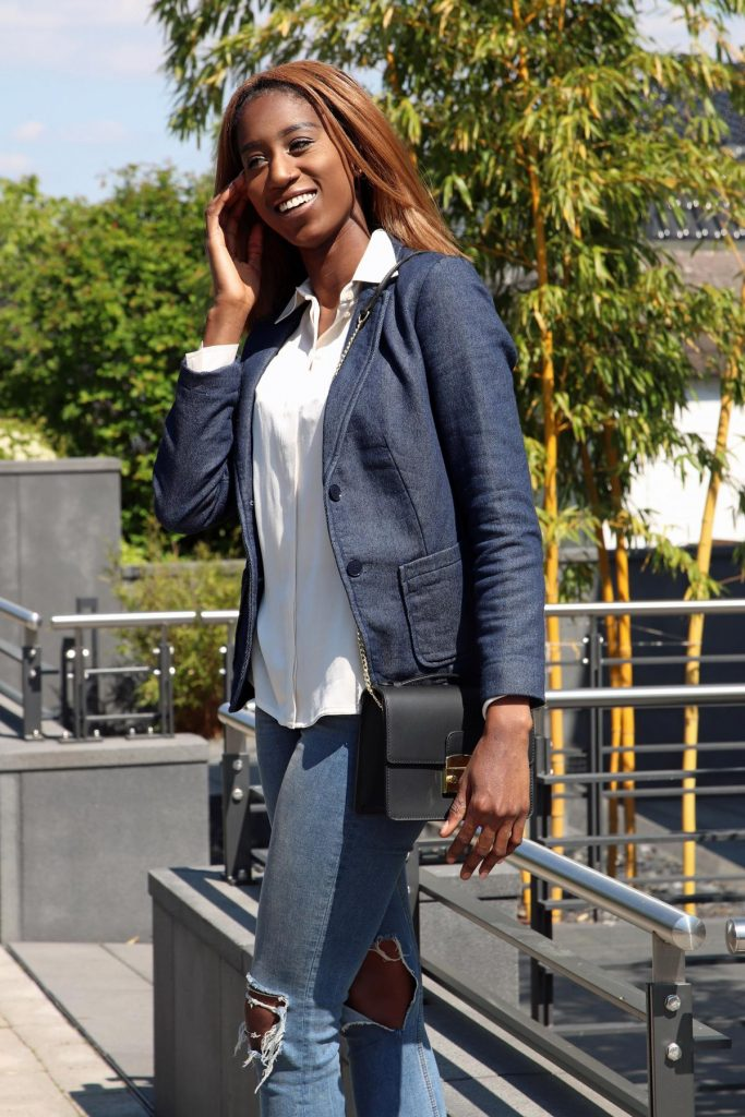 Bürostyle mit Denim-Blazer und destroyed denim Jeans mit cremefarbener Satinbluse und klassischer schwarzer Handtasche. © Copyright Bettina Katscher 2020