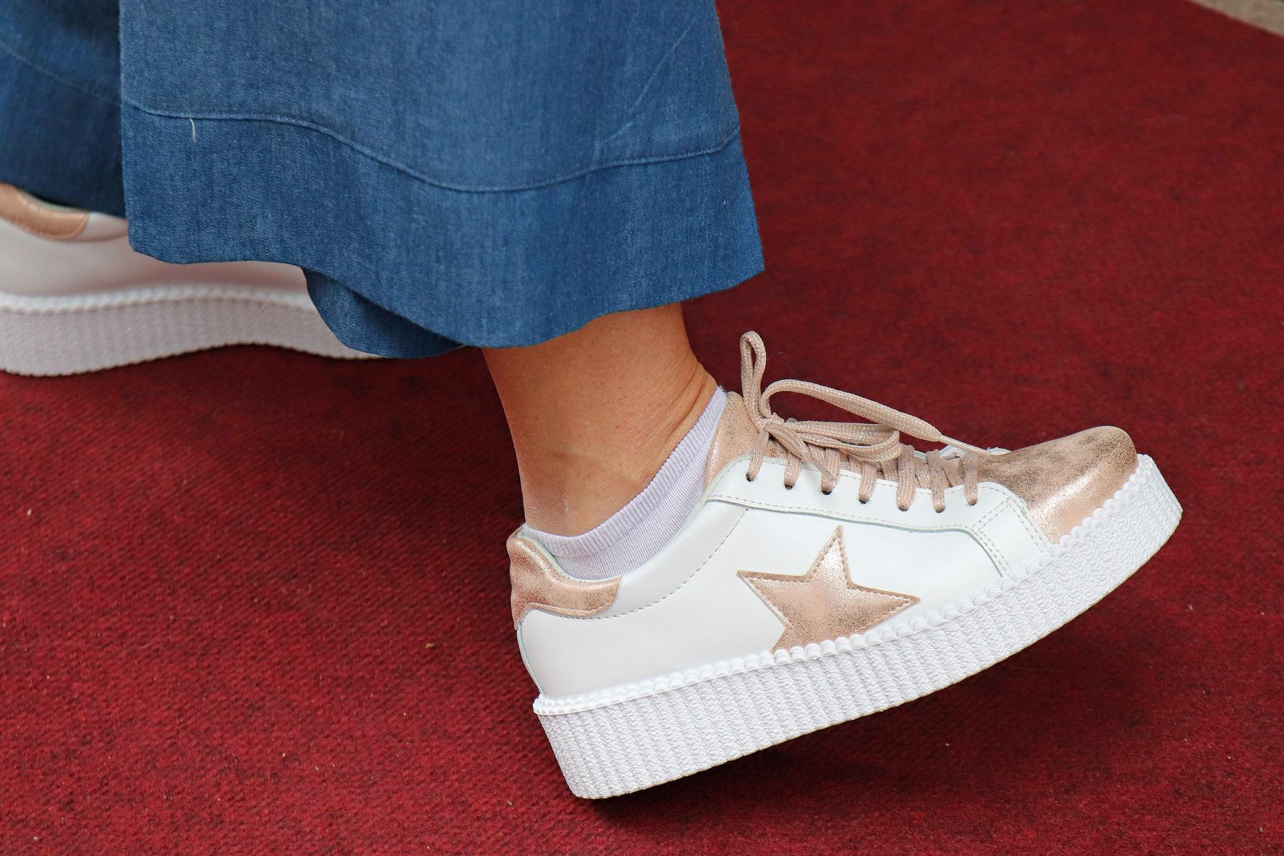 Flared Jeans und Sneaker mit Metallic machen das Rennen