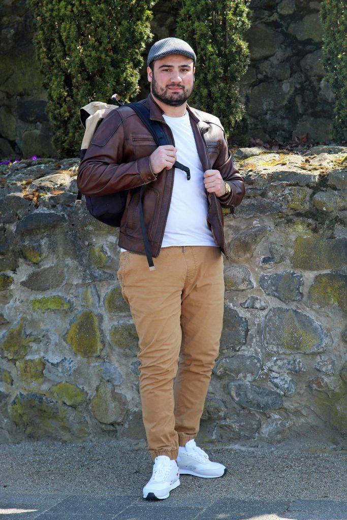 Lässiger Männerstyle mit beiger Hose mit Bündchen, Sneakern, karierter Kappe und Rucksack. © Copyright Bettina Katscher 2020