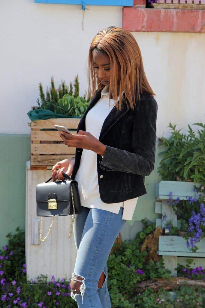 Casual Bürostyle mit Cord-Blazer und destroyed denim Jeans mit cremefarbener Satinbluse, Basic-Pullover und klassischer schwarzer Kasten-Handtasche mit Gliedergurt. © Copyright Bettina Katscher 2020