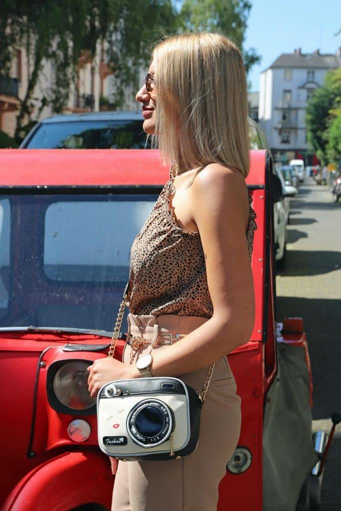 Damen-Sommerlook in Beigetönen mit gepunktetem One-Shoulder-Top, goldfarbenem eckigen Gliedergürtel, beiger Sommerhose und Fancy-Bag in Kameraform. © Copyright Bettina Katscher 2020