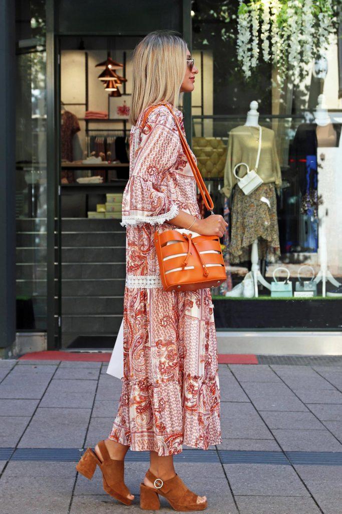 Sommer-Bloggerstyle mit langem Paisley-Kleid, cognacfarbenen Seventies-Sandalen mit Blockabsatz und orangener Handtasche mit Cut-Outs. © Copyright Bettina Katscher 2020