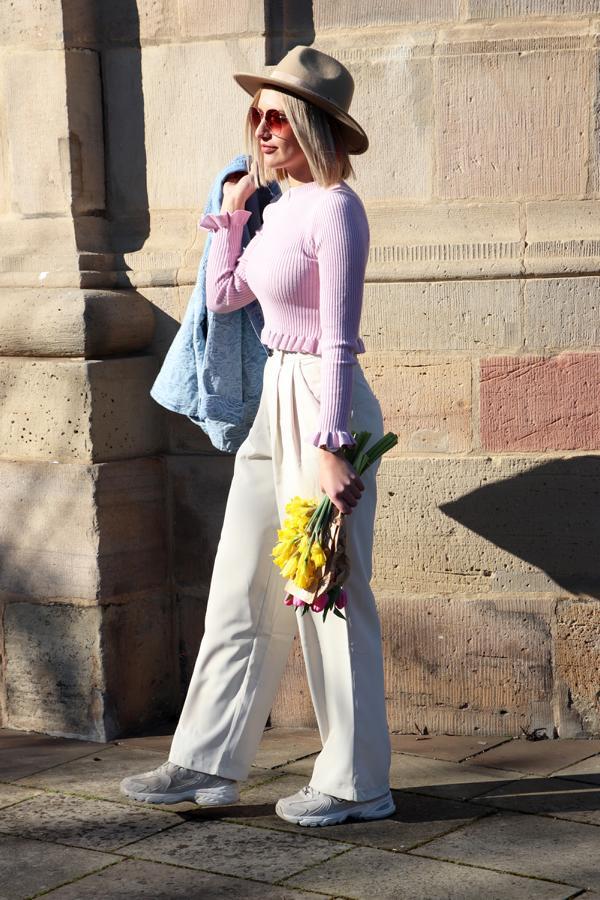 Casual Bloggerstyle: bedruckte Damen-Jeansjacke, dazu eine beige Stoffhose mit Bundfalten, fliederfarbener Pulli mit Volants und großer Fashion-Brille. © Copyright Bettina Katscher 2021